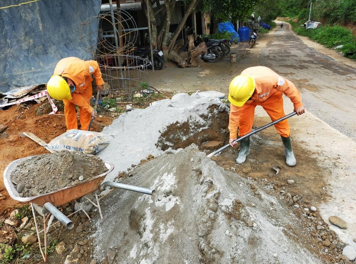 Công đoạn lấp hố, bê tông cứng trụ được triển khai tại chỗ bởi các công nhân điện lực. Ảnh: Đ.N