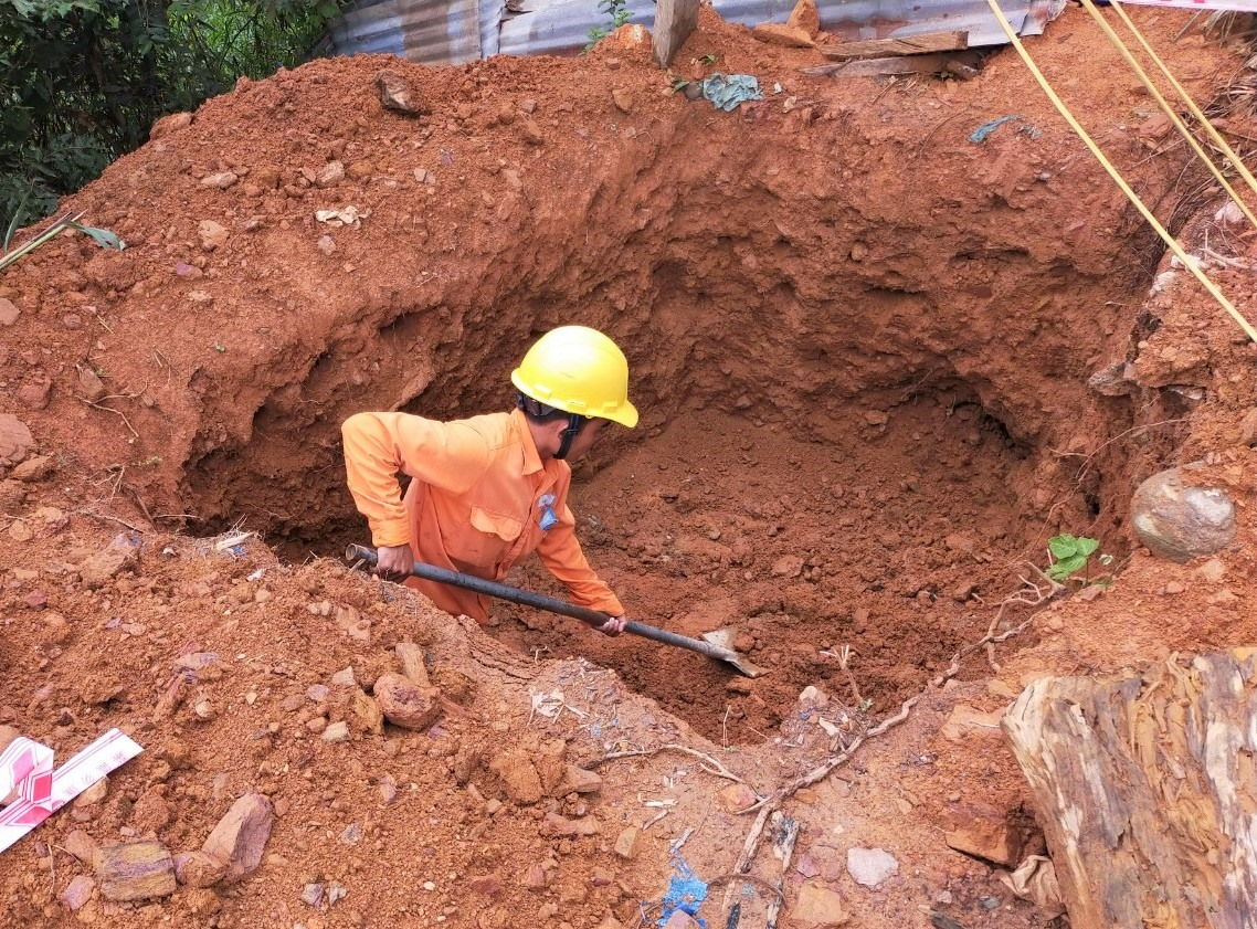 Nhiều ngày qua, các công nhân Điện lực Hiệp Đức đến tận khu tái định cư để đào hố chôn trụ điện. Ảnh: Đ.N