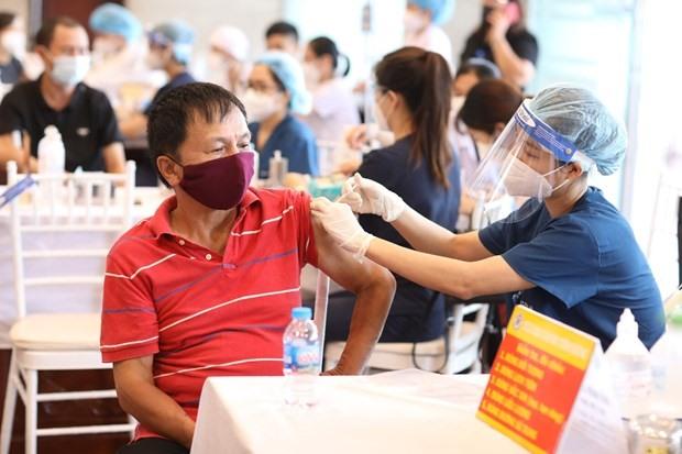 Nhân viên y tế tiêm vaccine phòng COVID-19 cho người dân quận Hoàn Kiếm. (Ảnh: Minh Quyết/TTXVN)