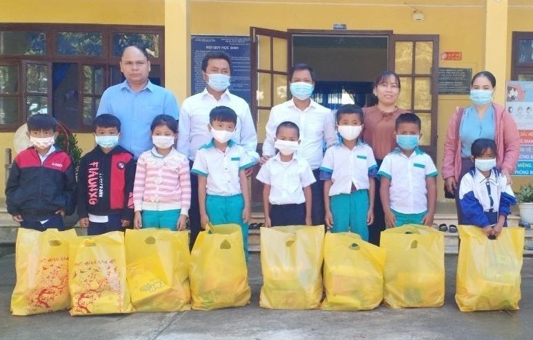 Phó chủ tịch UBND huyện Arất Blúi (giữa) tặng quà cho học sinh trường Tiểu học xã Lăng. Ảnh: ĐH
