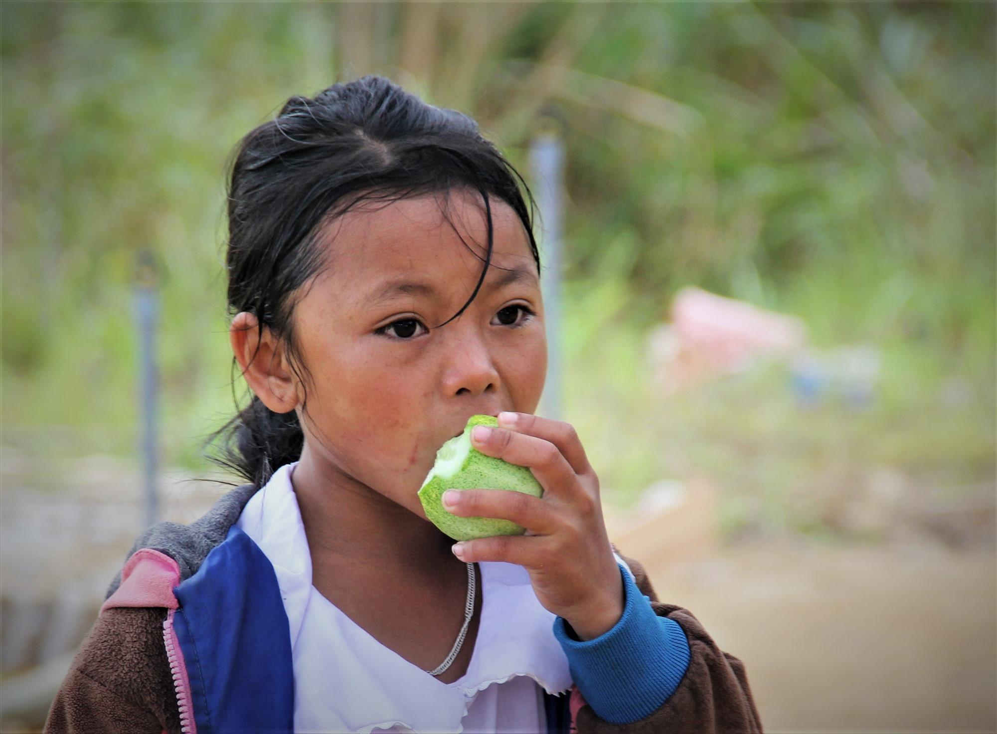 Một học sinh ở xã biên giới Ch'Ơm tranh thủ lót dạ bằng quả dưa trên đường đến lớp.