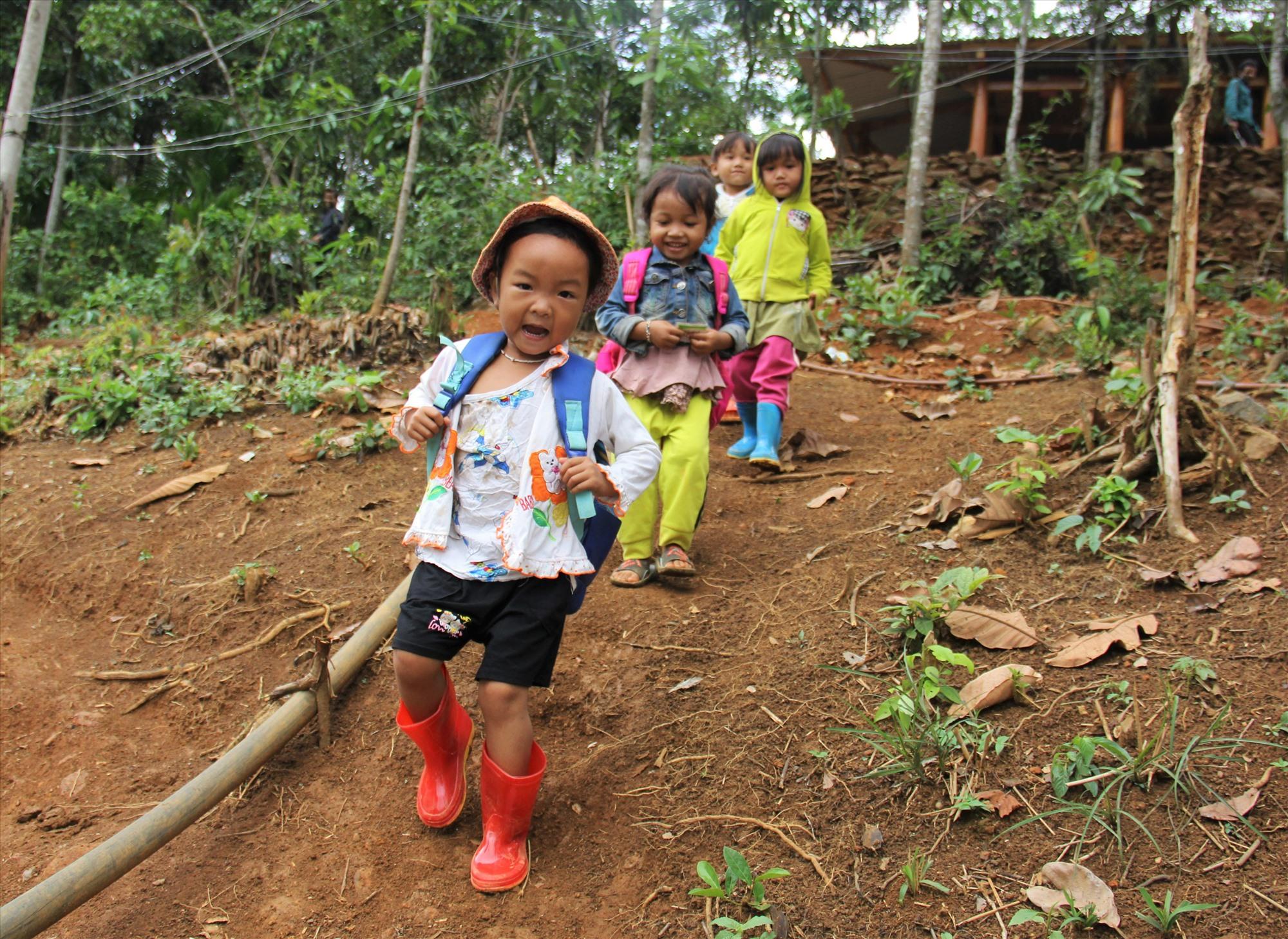Các em nhỏ người Xê Đăng ở nóc Long Bok (thôn 3, xã Trà Mai, Nam Trà My) trên đường về nhà sau buổi học. Để đi đường an toàn, cha mẹ đã sắm ủng cho các em.