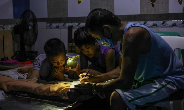 Petronilo Pacayra ( Quezon, Philippines) hướng dẫn cho các con học trực tuyến trong căn phòng chật chội và thiếu ánh sáng. Ảnh: Getty Images