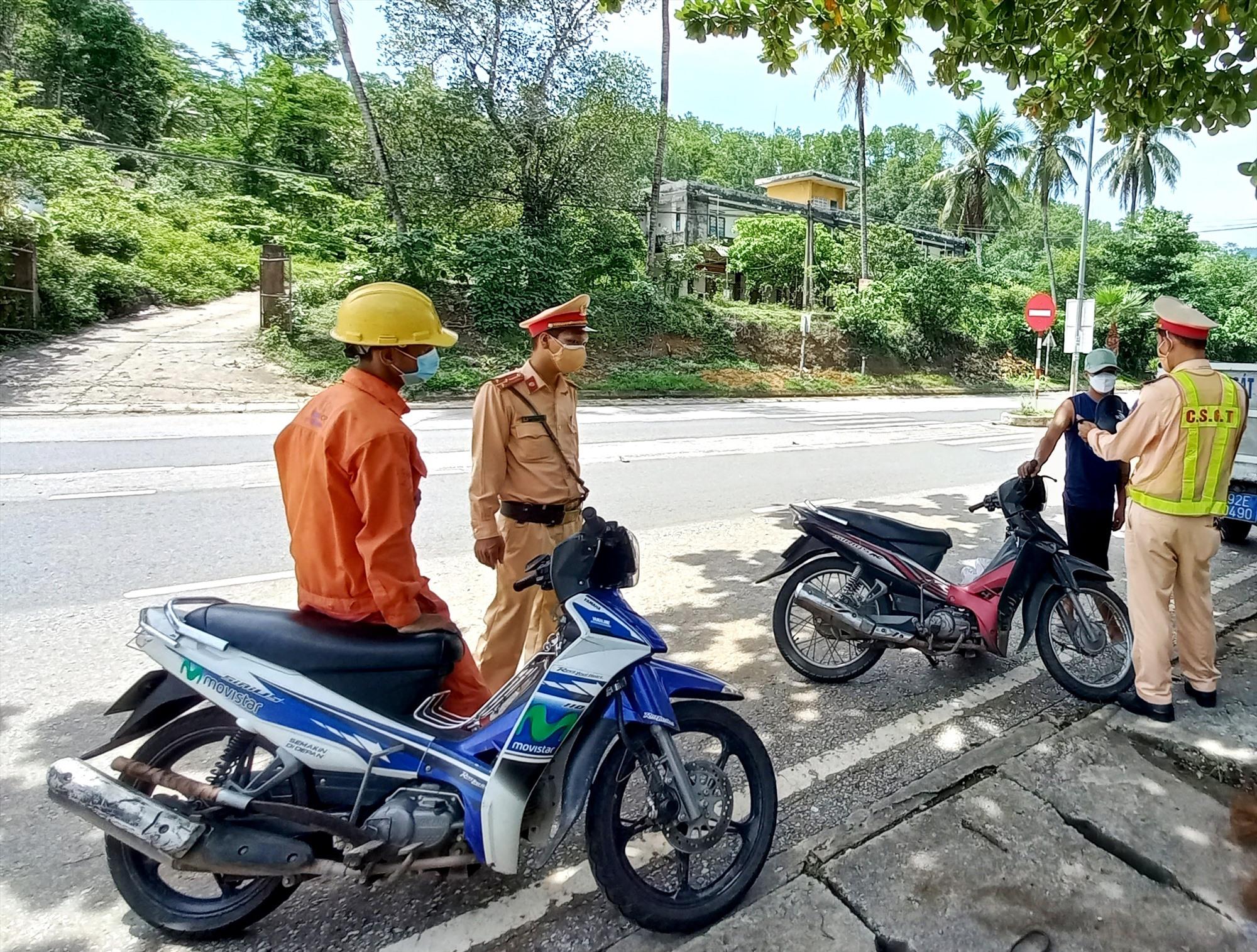 Một công nhân đội mũ bảo hộ lao động điều khiển xe máy bị lực lượng chức năng tuýt còi. Ảnh: S.C