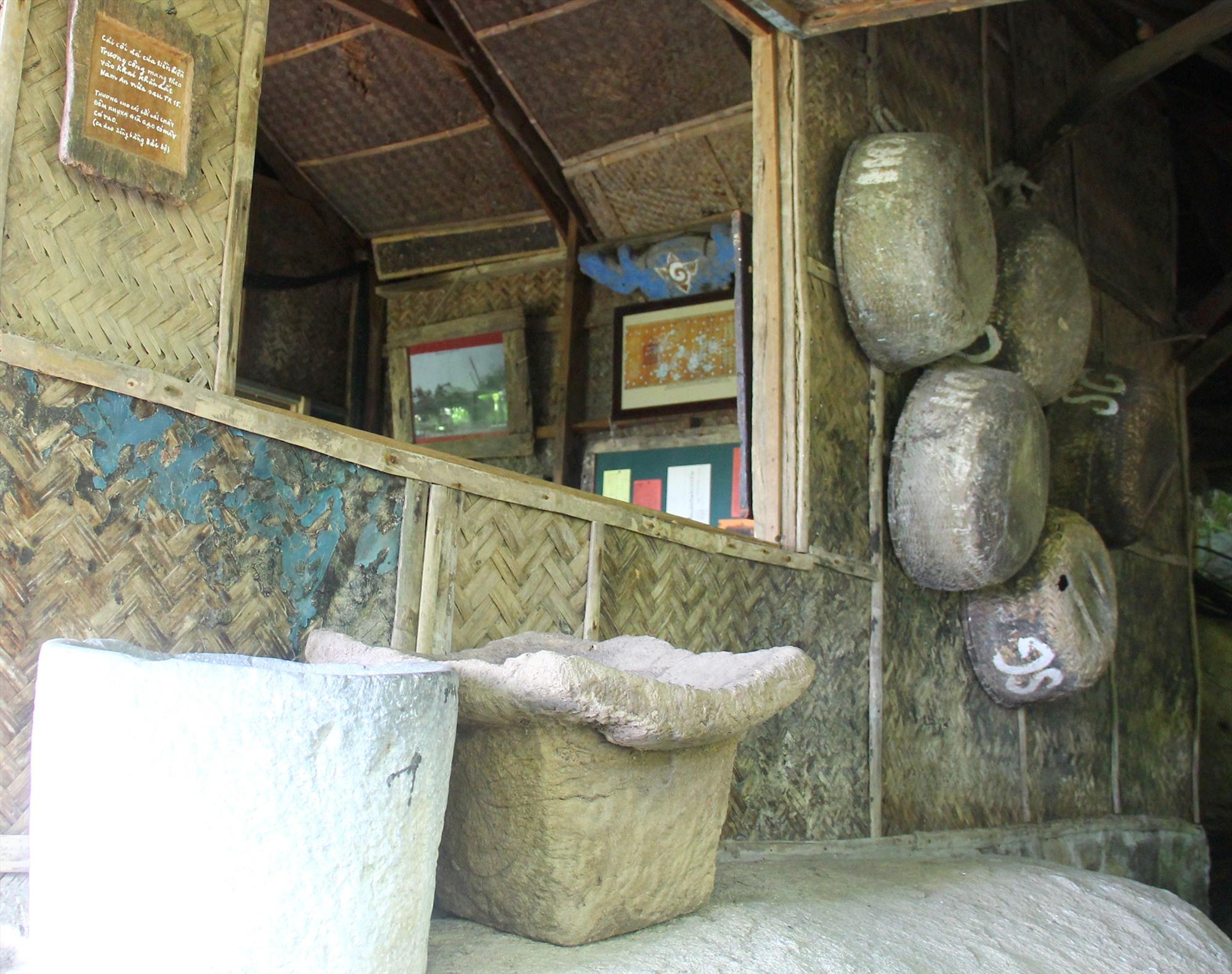 Chiếc cối đá lưu giữ tại Bảo tàng Đồng Đình, tấm bảng chép câu ca dao treo mé trên bên trái. Ảnh: H.X.H
