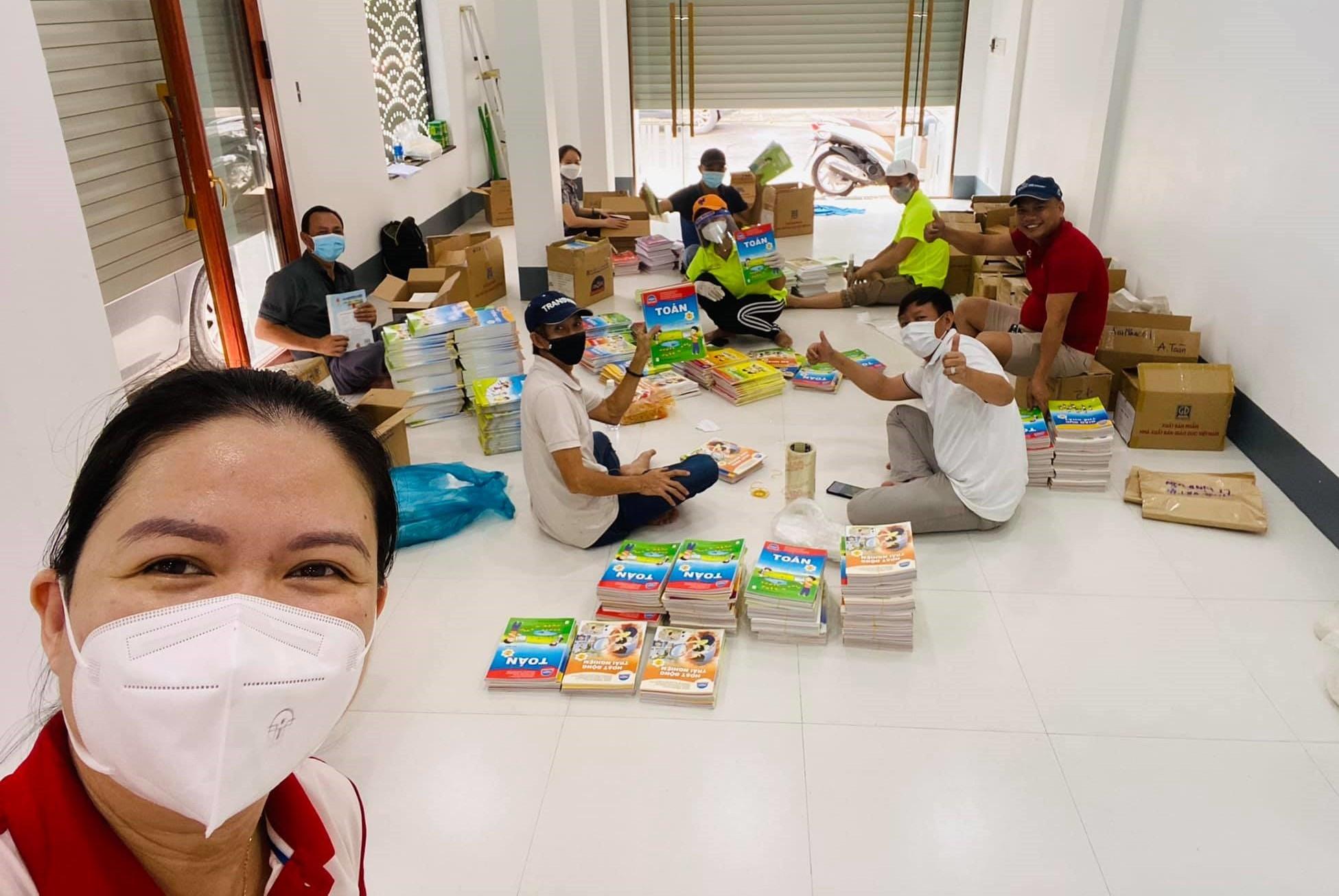 Thành viên QNB đóng gói sách trước khi trao tặng con em đồng hương. Ảnh: QNB