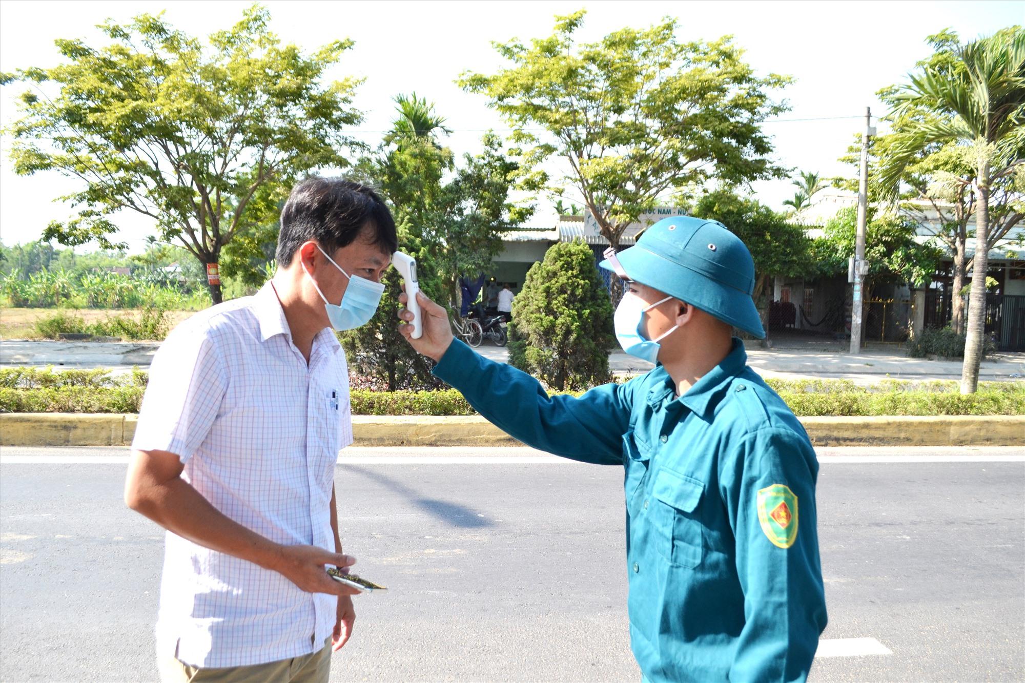 Duy trì kiểm soát y tế tại chốt kiểm soát trên đường Hùng Vương, thị trấn Ái Nghĩa. Ảnh: CT