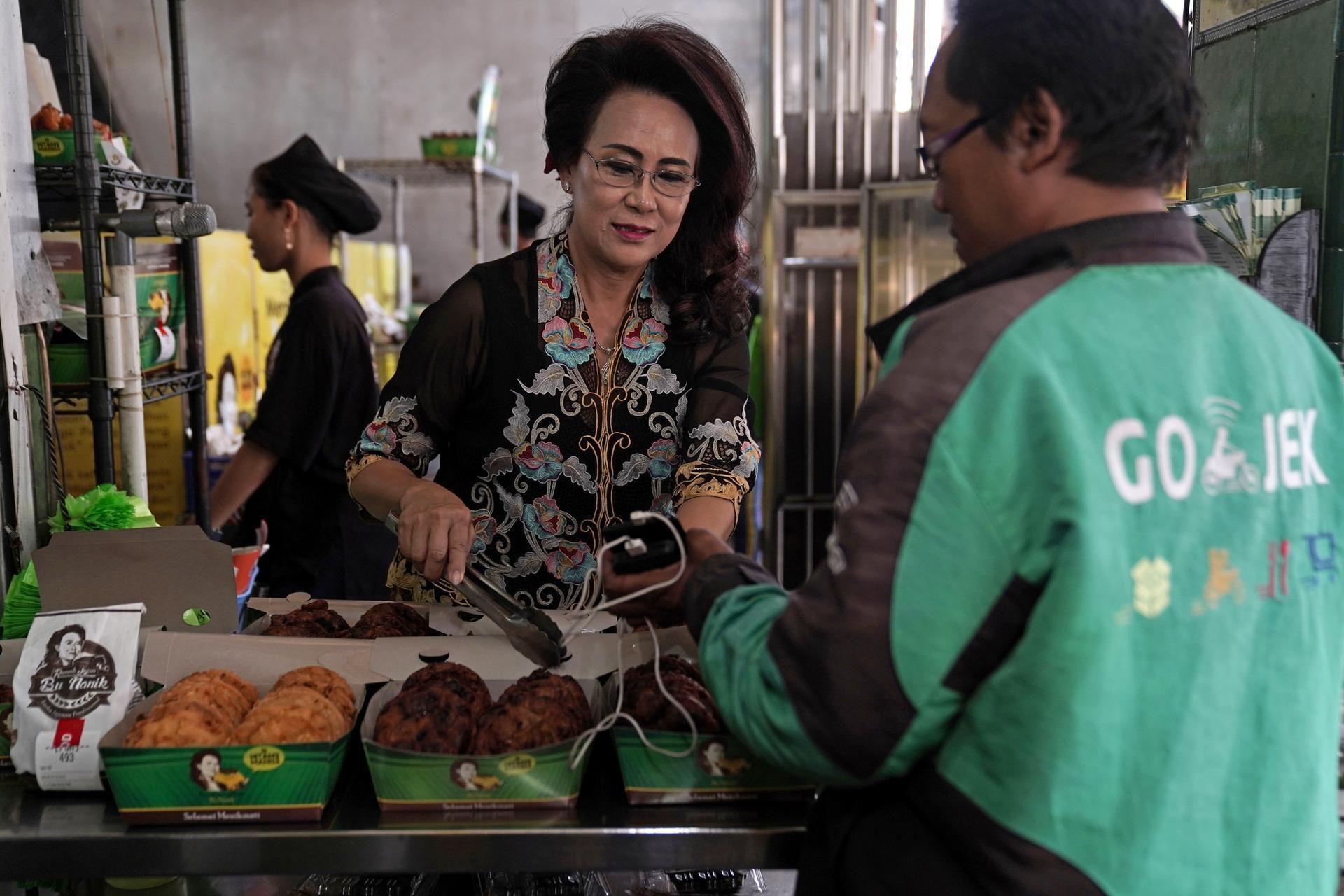 Tài xế công nghệ nhận đơn hàng tại quầy thực phẩm ở Jakarta, Indonesia. Ảnh: Bloomberg
