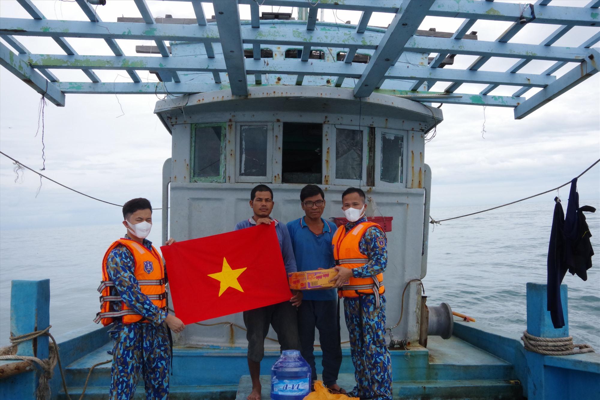 Tặng cờ Tổ quốc, thực phẩm cho ngư dân hoạt động trên vùng biển chủ quyền. Ảnh: T.C