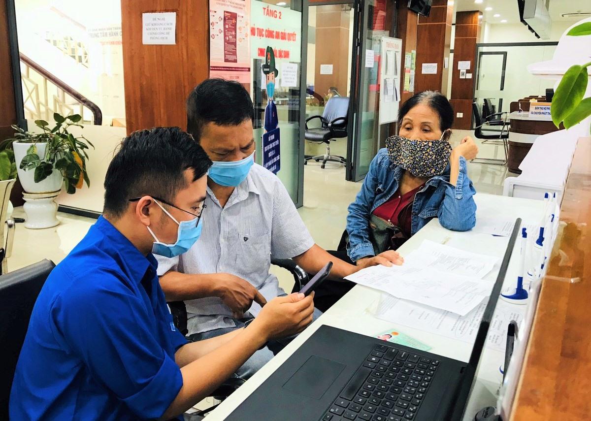 Đội Thanh niên xung kích của Thành đoàn Tam Kỳ tham gia hỗ trợ người dân nộp hồ sơ thủ tục hành chính trực tuyến tại Trung tâm Hành chính công thành phố. Ảnh: VINH ANH