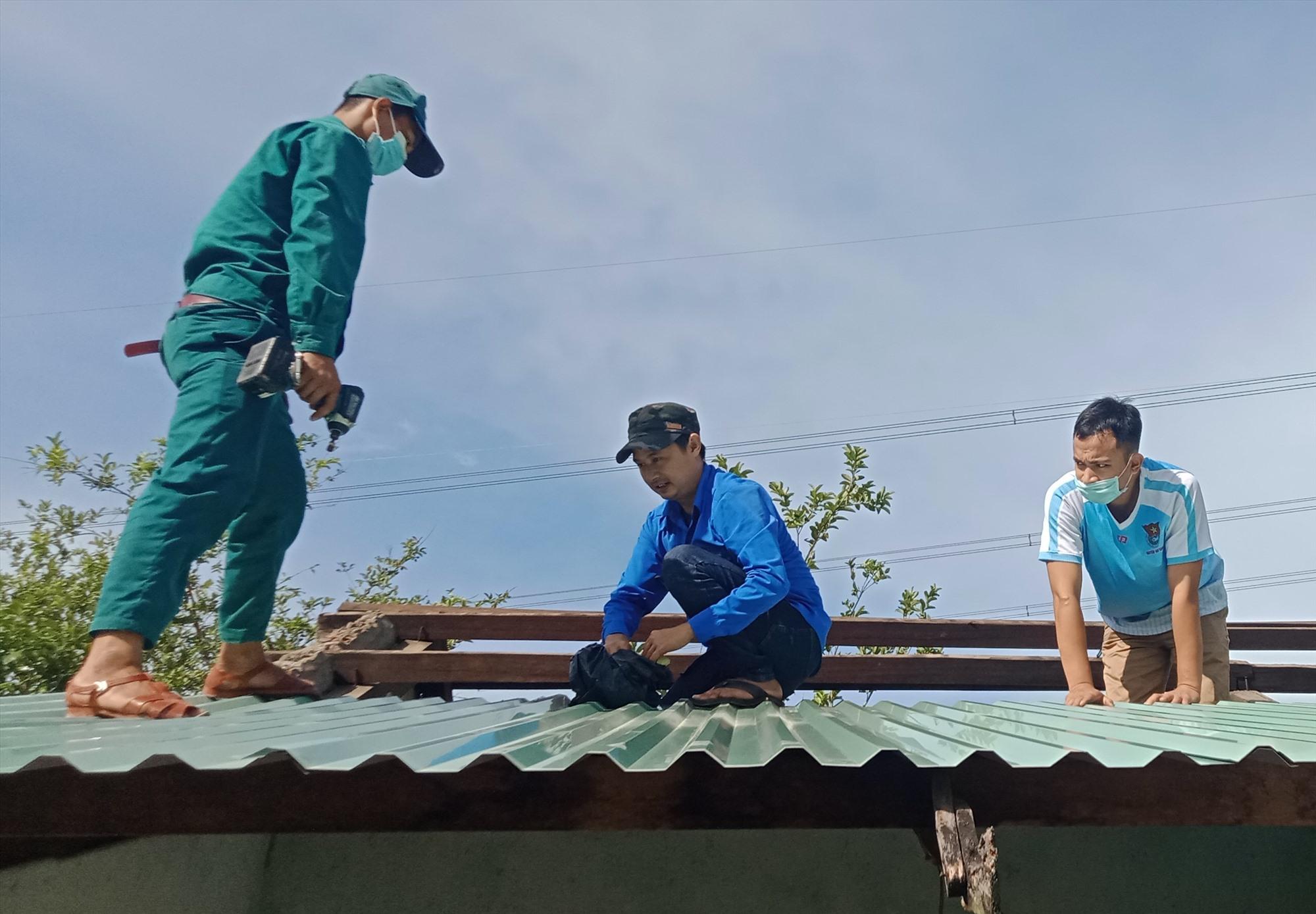 Đinh Quang Hòa (ở giữa) trong lần tham gia hỗ trợ Huyện đoàn Nam Giang tu sửa nhà chính sách. Ảnh: Đ.N