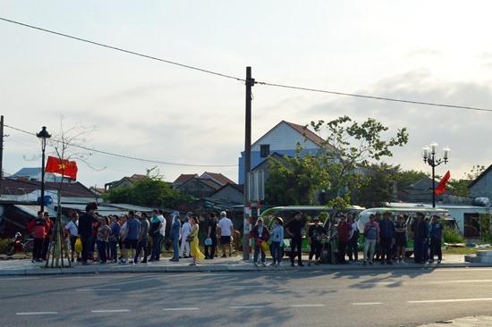 Khách chờ xe điện trung chuyển vào tham quan làng gốm Thanh Hà. Ảnh: K.L