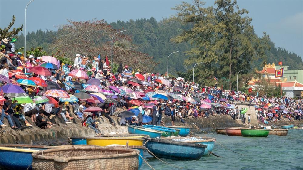 Trong bờ, hàng nghìn người cổ vũ cho đội thuyền đua xóm mình. Ảnh: XUÂN THỌ