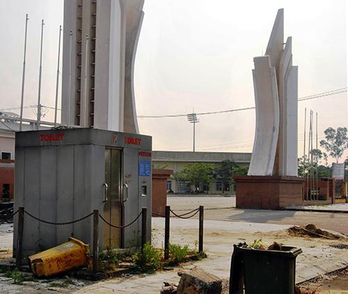 Nhà vệ sinh công cộng tự động và các thùng thu gom rác thải gây ô nhiễm môi trường trầm trọng trước khu vực cổng Trung tâm TDTT tỉnh.  Ảnh: ĐIỆN NGỌC