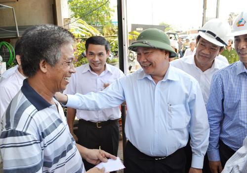 Phó Thủ tướng Nguyễn Xuân Phúc trò chuyện với người dân bị ảnh hưởng tại Núi Thành.Ảnh: CÔNG TÚ