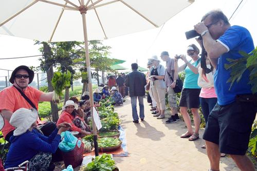 Du khách nước ngoài cũng tham gia hoạt động bán rau. Ảnh: V.L
