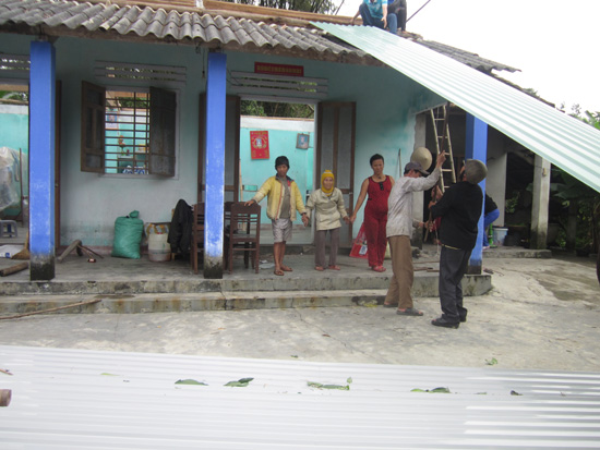 Sửa sang và lợp lại nhà cho bà Lê Thị Phẩm. Ảnh: B.M.P