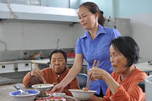 Chị Đinh Thị Minh Hội tận tình chăm lo từng bữa ăn cho người có công. Ảnh: HÀN GIANG