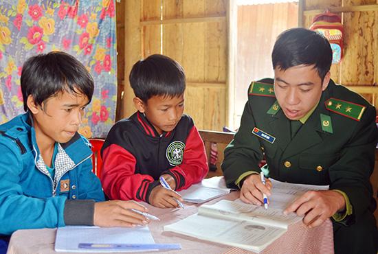 Trẻ em vùng biên học chữ cùng thầy giáo mang quân hàm xanh. Ảnh: ALĂNG NGƯỚC