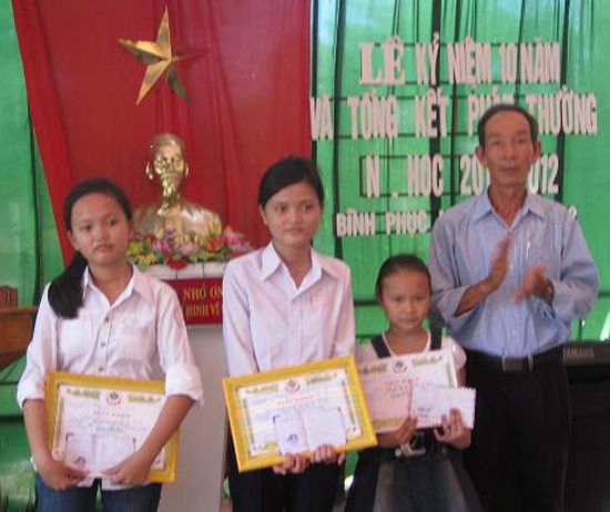 Ông Nguyễn Hữu Quang - Chủ tịch Hội Chữ thập đỏ kiêm Chủ tịch Hội Khuyến học xã Bình Phục (Thăng Bình) trao học bổng cho học sinh nghèo. Ảnh: THÚY ƯU