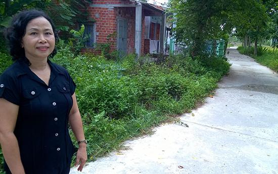 Cô giáo Nguyễn Thị Kim Hoa bên con đường bê tông dẫn vào tổ 8, thị trấn Hà Lam, Thăng Bình.  Ảnh: TRẦN ĐỨC