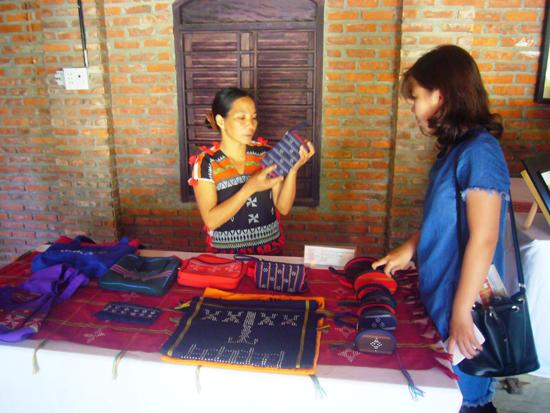 Du khách tham quan gian hàng trưng bày sản phẩm dệt thổ cẩm.