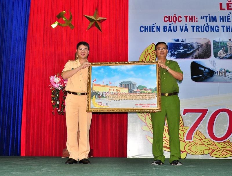 Trung tá Đỗ Thanh Bình - Phó Cục trưởng Cục CSGT tặng quà lưu niệm cho lãnh đạo nhà trường. Ảnh: VINH ANH