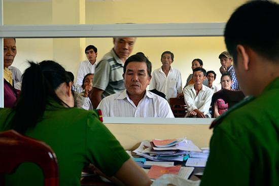 Cán bộ Công an thị xã Điện Bàn xử lý hồ sơ liên quan đến hộ khẩu cho người dân. Ảnh: XUÂN KHÁNH