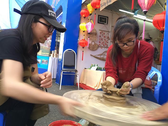 Các bạn trẻ thích thú với gian hàng gốm Thanh Hà. Ảnh: HA CHI