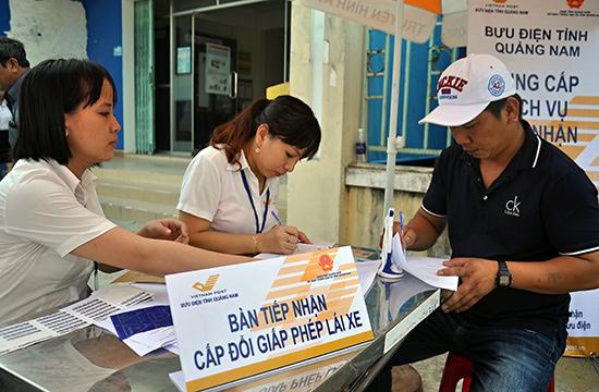 Người dân đến làm thủ tục cấp đổi GPLX tại Bưu cục Điện Ngọc. Ảnh: VINH ANH