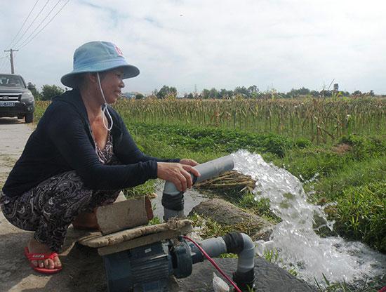 Người dân thôn Chiêm Sơn (Duy Sơn, Duy Xuyên) tự bỏ tiền đóng giếng để bơm nước cứu lúa. Ảnh: VĂN SỰ
