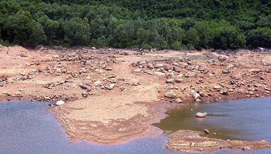 Lượng lớn đất đá đang bồi lấp nghiêm trọng lòng hồ chứa nước Suối Tiên. Ảnh: VĂN SỰ