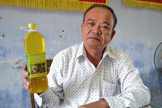 """Ông Nguyễn Đức Thành với sản phẩm dầu phụng được đóng chai mang thương hiệu """"Đất Quảng"""". Ảnh: C.T"""