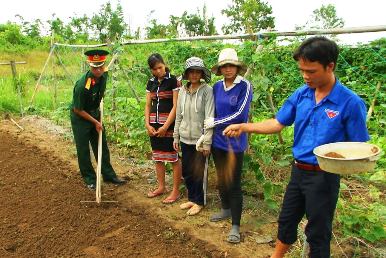 Các trí thức trẻ hướng dẫn đồng bào biên giới cách gieo trồng vườn rau sạch. Ảnh: T.A