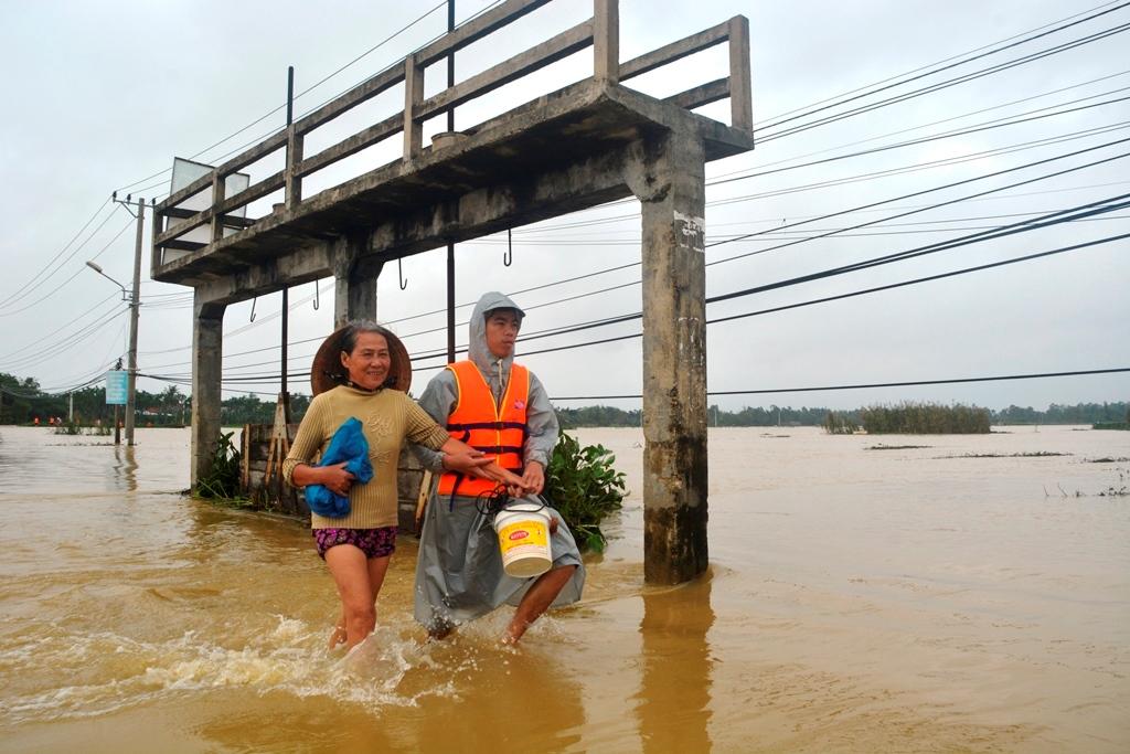 Đưa một bà cụ qua đường đang có nước chảy xiết. Ảnh: XUÂN THỌ