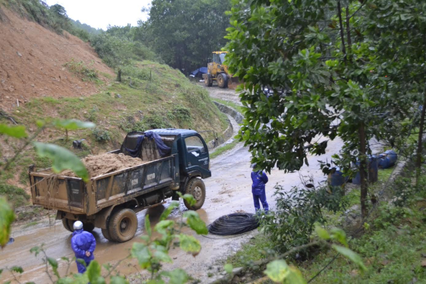 Xe tải di dời đất đá bị sạt lở khỏi đường. Ảnh: CÔNG TÚ