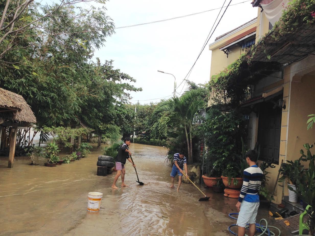 Người dân tranh thủ dọn bùn khi nước vừa rút. Ảnh: MINH HẢI