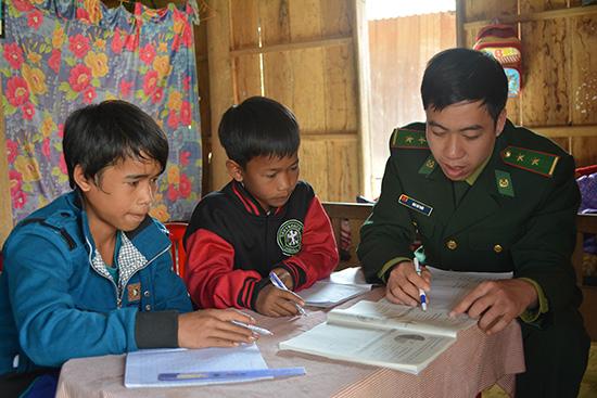 Người lính biên phòng vùng biên đến tận nhà chỉ bảo các em học tập.