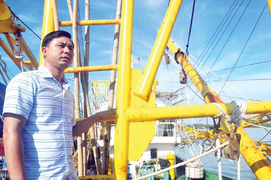 Ngư dân Huỳnh Ngọc Huệ bên tăng gông chụp mực. Ảnh: QUANG VIỆT