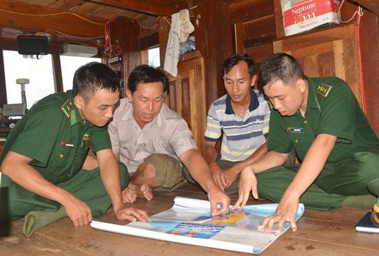 Các chiến sĩ Đồn Biên phòng Cửa khẩu cảng Kỳ Hà thông tin về chủ quyền vùng biển cho ngư dân trước ngày ra khơi. Ảnh: ALĂNG NGƯỚC