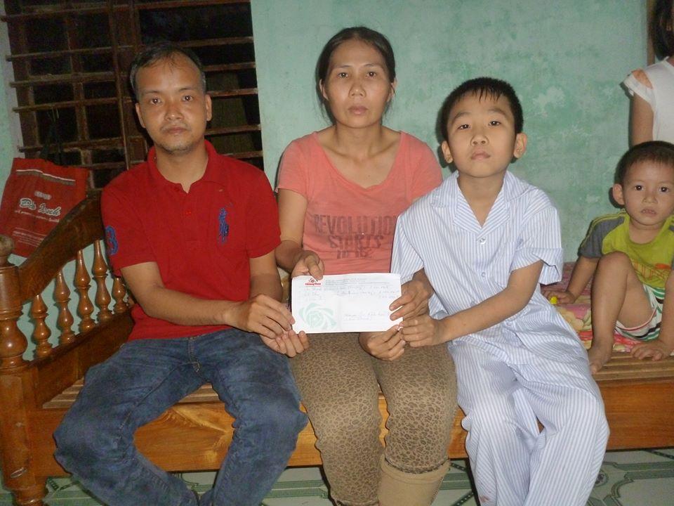 Tác giả bài viết trao tiền cho gia đình cháu Trương Văn Bảo. ảnh: C.N