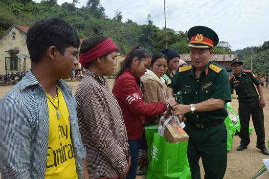 Đại tá Đoàn Thế Tùng - Phó Chính ủy Bộ CHQS tỉnh tặng quà cho bà con các bộ tộc Lào anh em. Ảnh: T.TUẤN