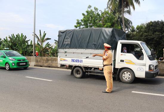 Cán bộ Trạm CSGT Thăng Bình tổ chức tuần tra, chốt chặn để xử lý các hành vi vi phạm về tốc độ của phương tiện trên tuyến quốc lộ 1 sáng 11.5. Ảnh: T.CÔNG