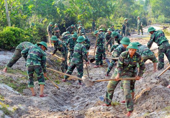 Cán bộ chiến sĩ BĐPB giúp dân làm công trình nông thôn mới.  Ảnh: ALĂNG NGƯỚC