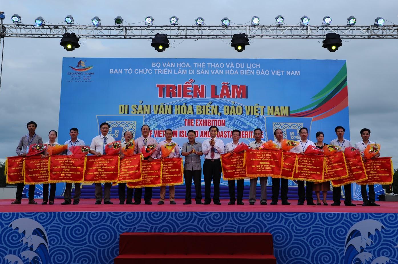 Ban tổ chức tặng cờ lưu niệm cho 14 tỉnh thành tham gia triển lãm. Ảnh: MINH HẢI