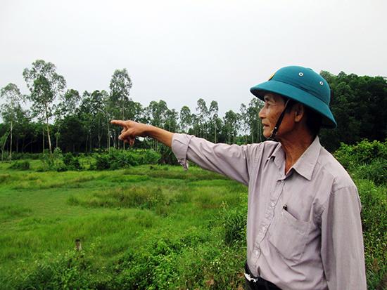Ông Đinh Bốn - Bí thư Chi bộ thôn An Trung chỉ tay về phía những chân ruộng bị đất bồi lấp, phải bỏ hoang từ 3 năm nay.Ảnh: VĂN SỰ