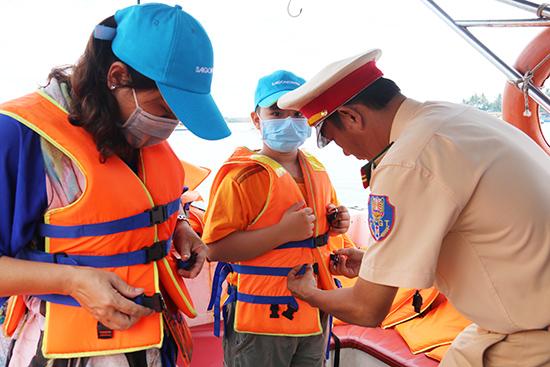 Lực lượng cảnh sát giao thông kiểm tra, nhắc nhở hành khách mặc áo phao khi lên tàu.  Ảnh: THÀNH CÔNG