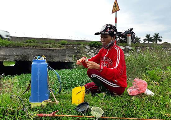 Bà Trần Thị Bình chuẩn bị phun thuốc để diệt rầy. Ảnh: Biên Thực