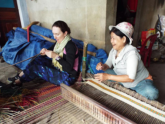 A visitor experiences sedge mat making with a local resident via Cultures Connect