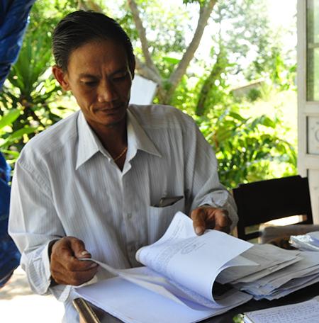 Ông Lê Nguyên Hoàng xem lại hồ sơ gửi cơ quan chức năng. Ảnh: H.G